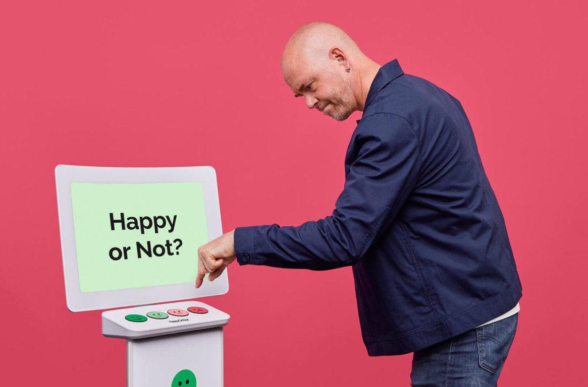 Man pressing a smiley button